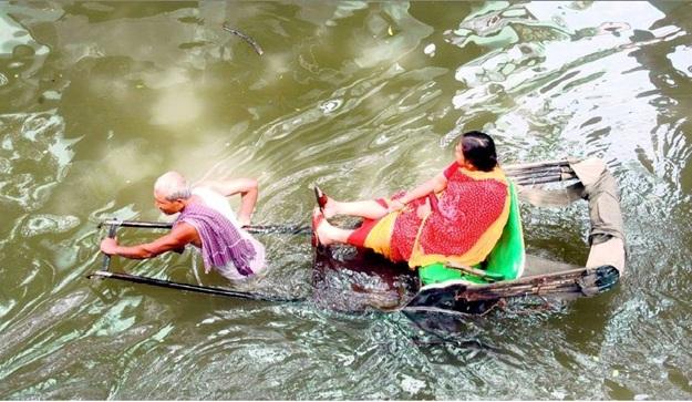 Kolkata's waterlogged streets, hand-pulled rickshaws in water